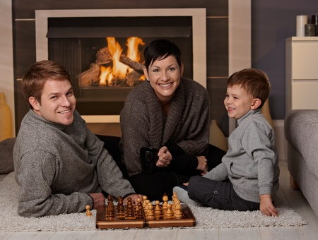 Happy family playing chess at home in a cold winter day, looking at camera, smiling. photo