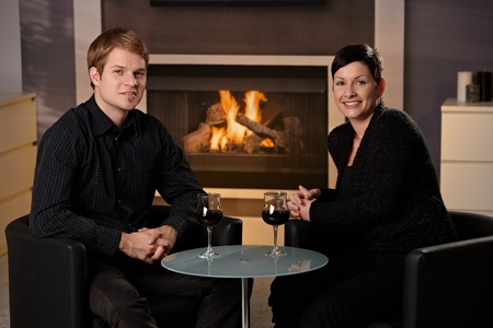 Young romantic couple dating, sitting in front of fireplace at home, drinking red wine. Stock Photo - 8752507