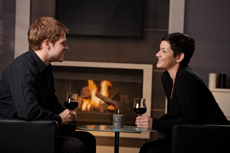 Young romantic couple dating, sitting in front of fireplace at home, drinking red wine. photo