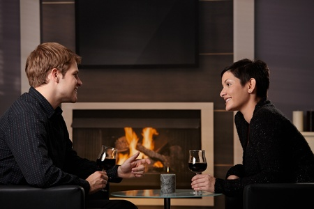Young romantic couple dating, sitting in front of fireplace at home, drinking red wine. Stock Photo - 8752502
