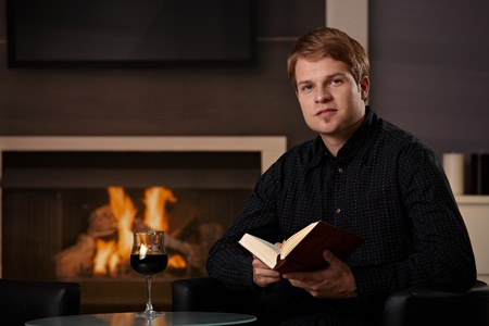 Young man sitting in front of fireplace at home on a cold winter day, reading book. Stock Photo - 8752501