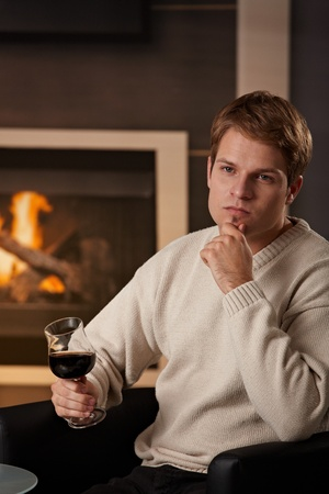 Young man sitting on sofa at home on a cold winter day, drinking red wine, thinking. photo