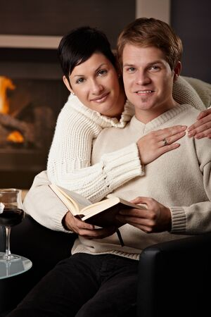 Happy young couple hugging in front of fireplace at home, looking at camera, smiling. photo