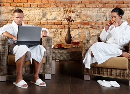 Couple enjoying wellness room in bathrobe, sitting together in armchair, using laptop computer, having tea. photo