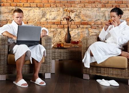 Couple enjoying wellness room in bathrobe, sitting together in armchair, using laptop computer, having tea. Stock Photo - 8753307