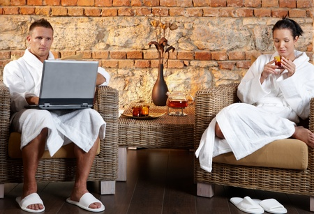 Couple relaxing in wellness, having tea, using laptop computer, sitting in armchair in bathrobe, photo
