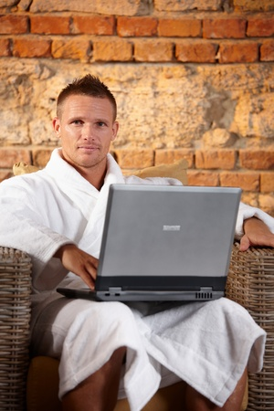 Portrait of handsome man in bathrobe sitting in armchair with laptop computer. photo