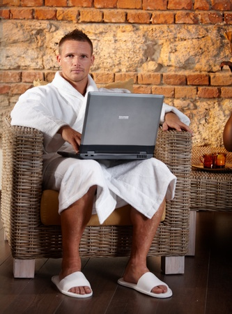 Portrait of relaxing man sitting in armchair with laptop computer, wearing bathrobe. Stock Photo - 8753411
