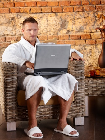 Portrait of man wearing bathrobe using laptop computer in armchair, relaxing in wellness. photo