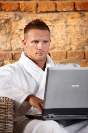 Handsome man looking at laptop computer screen, sitting in bathrobe. photo