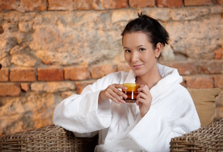 Young woman sitting in armchair in bathrobe, having tea, smiling at camera. photo