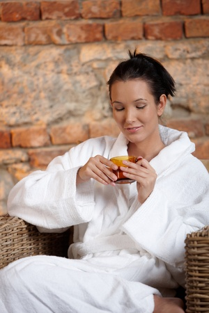 Woman wearing bathrobe, relaxing in wellness, enjoying tea. photo