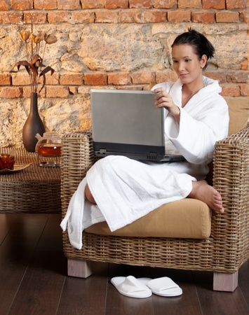 Young woman wearing bathrobe relaxing, using laptop computer, sitting in armchair. photo