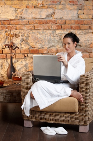 Portrait of woman in bathrobe sitting in armchair with laptop computer, smiling. photo