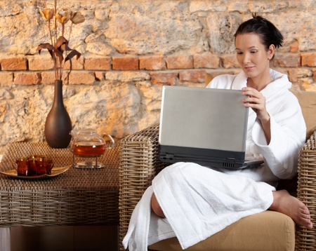 Woman in wellness environment sitting in armchair using laptop computer. photo