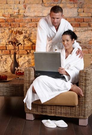 Couple in wellness wearing bathrobe using laptop computer.