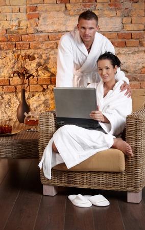 wellness environment: Portrait of bathrobe couple with laptop in wellness environment, smiling at camera.