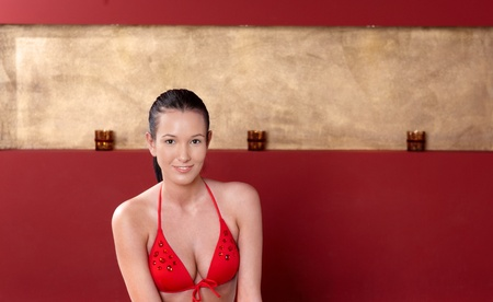 Portrait of pretty woman in red bikini swimsuit, smiling at camera. photo