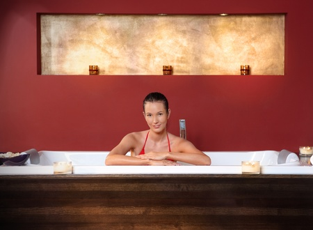 Portrait of young woman posing in bikini in wellness bath, smiling at camera. photo