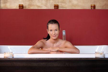 Young woman wellness bathing, smiling, looking at camera. photo