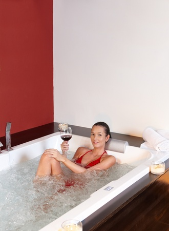Pretty woman enjoying lying in bubble bath with glass of wine, smiling, wearing red bikini. photo