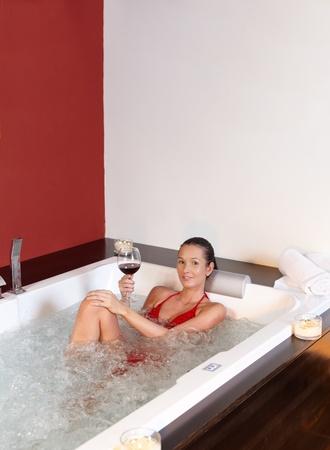 Pretty woman enjoying lying in bubble bath with glass of wine, smiling, wearing red bikini. photo