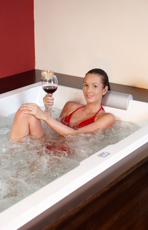 vin chaud: Portrait de femme jouissant de mieux-être en maillot de bain, boire du vin dans le bain à remous
