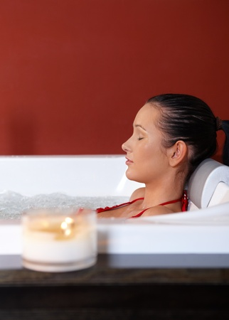 lying in bathtub: Portrait of woman enjoying hot tub with eyes closed.%uFFFD