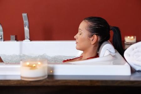 fürdő: Young woman enjoying wellness bubble bath with eyes closed in candle light.
