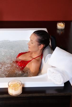 pretty woman in bikini relaxing lying in hot tub in wellness.%uFFFD photo