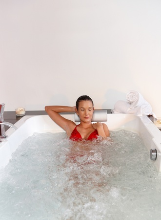 Portrait of pretty woman wearing bikini relaxing in hot tub.%uFFFD photo