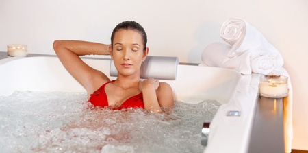 Young woman in red swimsuit enjoying hot tub with closed eyes.%uFFFD photo