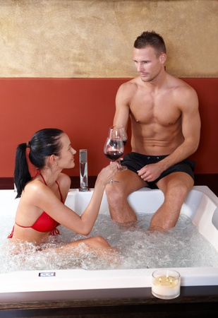 couple bathroom: Couple having fun in hot tub, toasting with red wine.%uFFFD