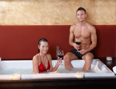 Portrait of happy couple having wine in hot tub, smiling at camera.%uFFFD photo