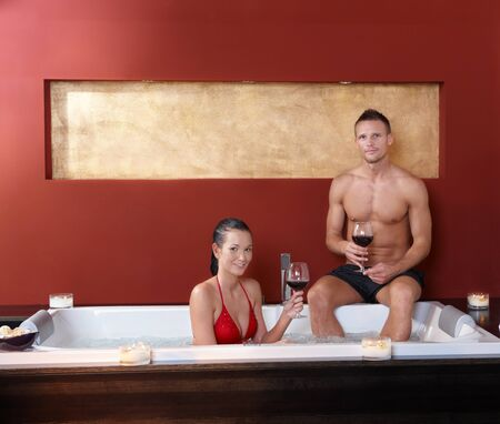 Portrait of happy couple in wellness hot tub enjoying red wine, smiling.%uFFFD photo