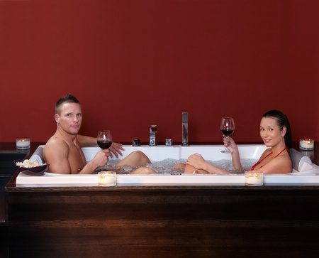 Couple sitting in bubble bath, having red wine in wellness environment, looking at camera. photo