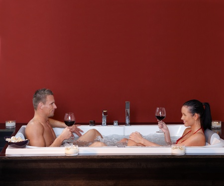 couple bathroom: Happy couple sitting in pool together, drinking red wine, smiling.%uFFFD