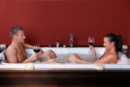 enjoy space: Young couple on wellness program sitting in hot tub bath, having red wine.%uFFFD Stock Photo