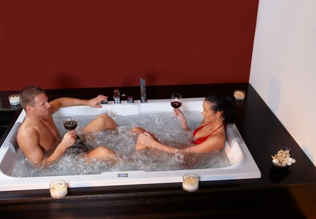 wife of bath: Couple enjoying hot tub and red wine, relaxing on wellness weekend, high angle view.%uFFFD Stock Photo