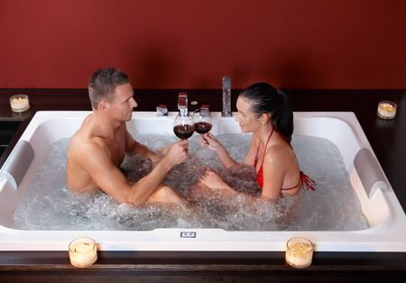 Couple celebrating in hot tub, clinking wine glasses, smiling.%uFFFD photo