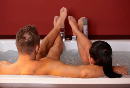 lying in bathtub: Young couple lying in hot tub with feet up, man embracing woman.%uFFFD