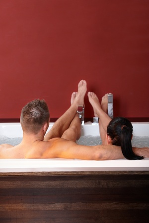 lying in bathtub: Couple in wellness hot tub with feet up, relaxing.%uFFFD