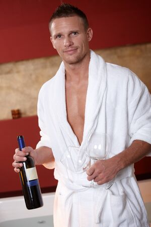 Smiling man wearing bathrobe on wellness trip holding wine bottle and glasses. photo