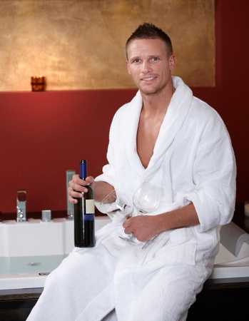 bathrobe: Happy man at hot tub sitting in bathrobe, holding wine bottle and glasses, smiling at camera.%uFFFD