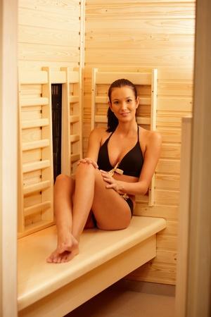 vertical wellness: Pretty woman wearing bikini sitting in sauna, smiling at camera.