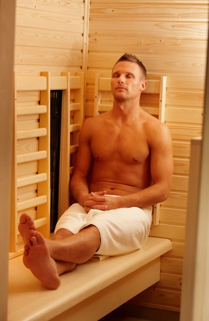 Sporty man enjoying sauna in towel, sitting with eyes closed. Stock Photo - 8753312