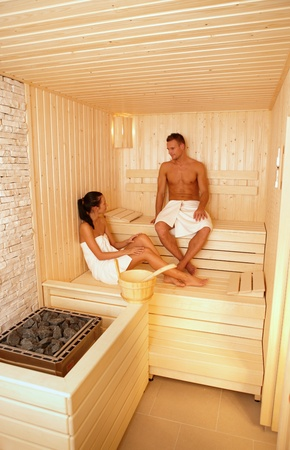 Young couple wearing towel talking in sauna, relaxing. photo