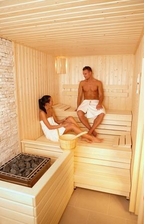 vertical wellness: Young couple wearing towel talking in sauna, relaxing.