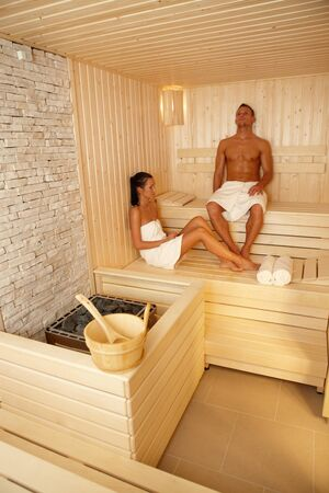 vertical wellness: Couple relaxing in sauna on wellness trip, enjoying healthy program. Stock Photo