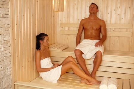 Couple relaxing in sauna with eyes closed. photo